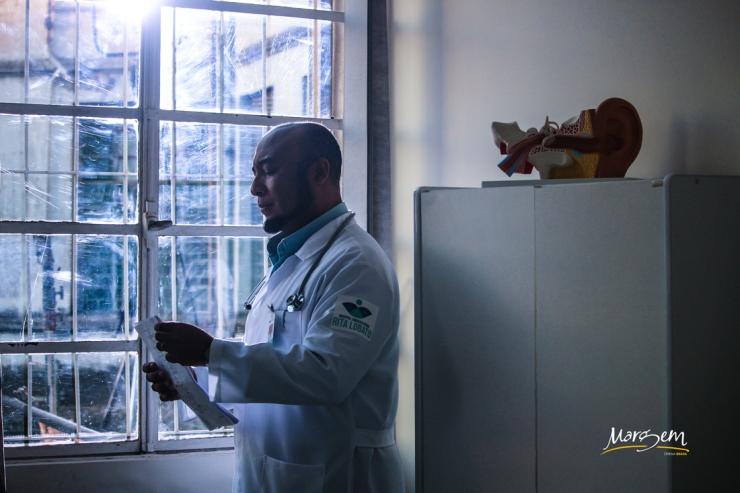 Álvaro RosaCosta encenando o Dr. Roberto na série Lua em Câncer da Margem Cinema Brasil para a TVE. Na imagem, ele está parado de perfil em frente a uma janela do hospital Rita Lobato, usando seu jaleco e lendo um documento. Do lado de fora, uma luz forte desenha o contorno do seu perfil.